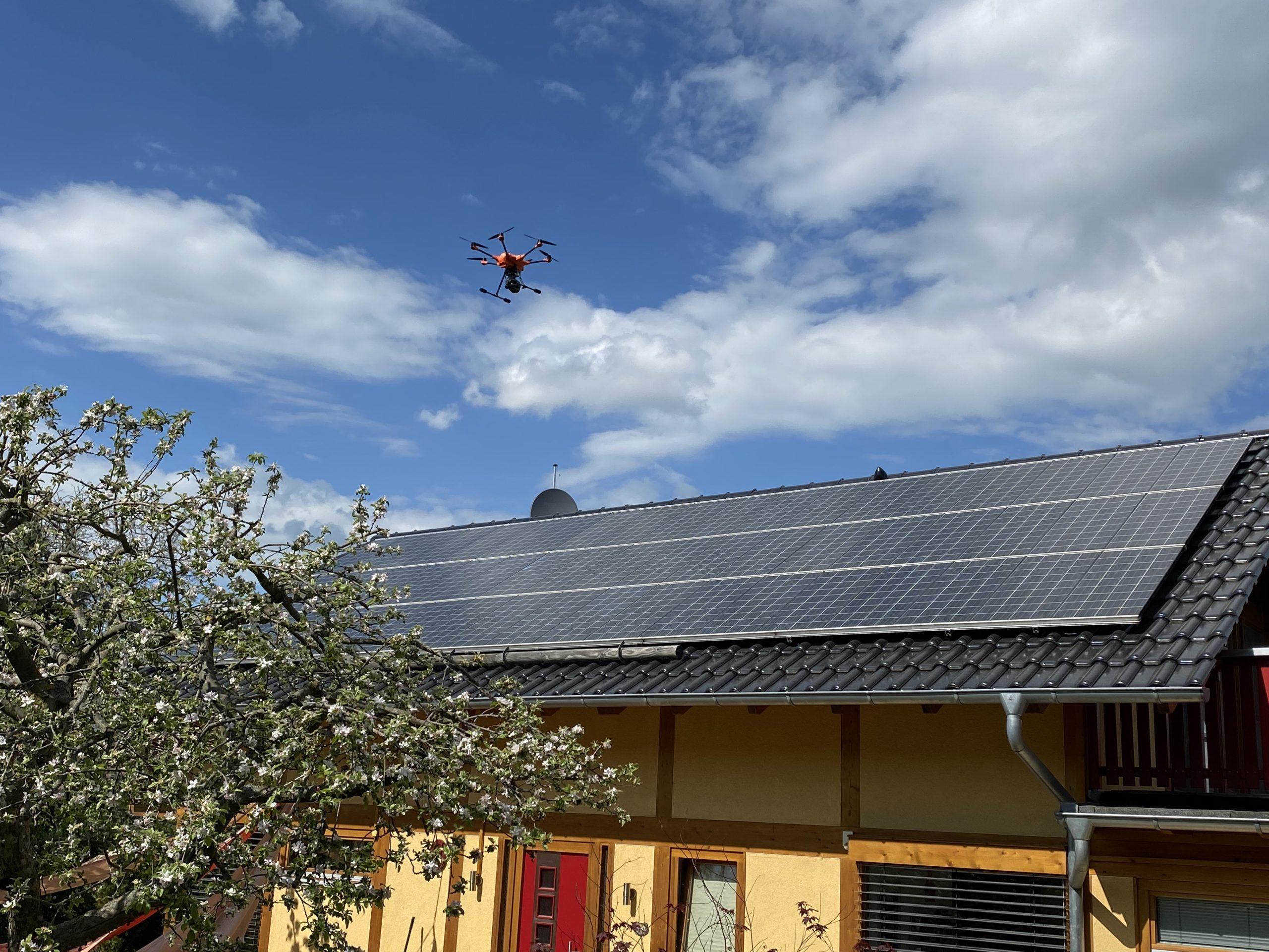 Drohne fliegt zur Vermessung der Solarfläche über das Haus
